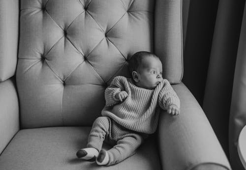A Cute Toddler Sitting on a Chair