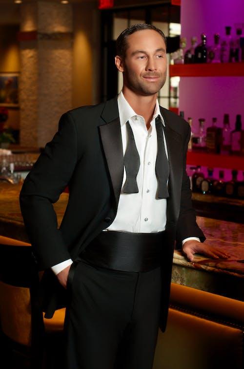 A Man in a Black Tuxedo at the Bar Counter