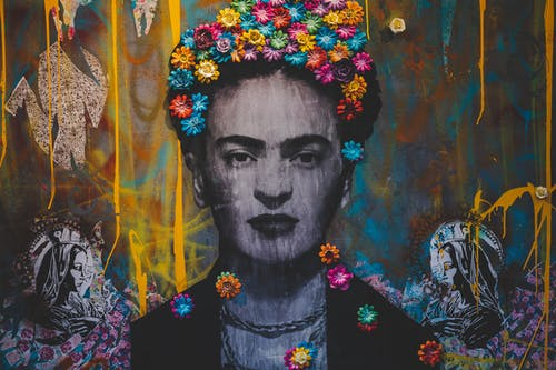 Creative artwork with Frida Kahlo painting decorated with colorful floral headband on graffiti wall