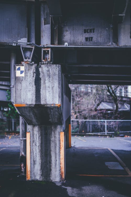 Old shabby concrete beam of weathered bridge located in industrial area of city on cloudy day
