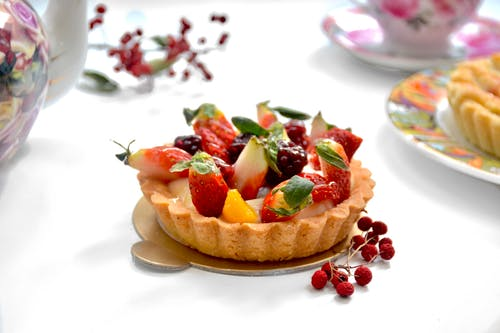 Tasty tarlet decorated with ripe strawberries on table with fresh berries near tea set on blurred background in light kitchen