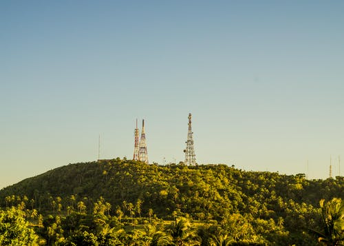 Metal tall telecommunication towers on high hills covered with tropical trees with fresh verdant foliage under cloudless sky
