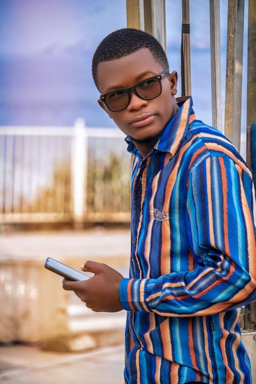 A Stylish Man Holding a Cellphone