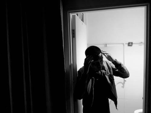 Man touching head in bathroom doorway