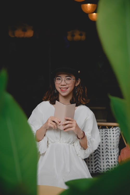 Woman in White Dress Holding a Wallet and Smiling