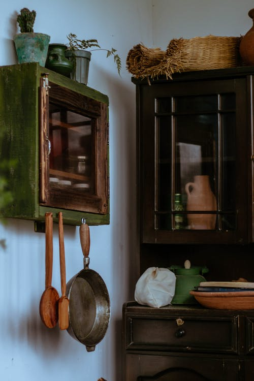 Room interior with wooden cupboard with potted plants and kitchenware near commode with various utensils and pot in light retro apartment