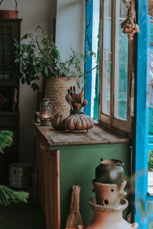 Room interior with various ceramic pots near windowsill with potted green plant and kitchenware near old kerosene lamp in daylight