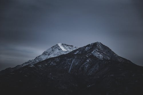 Amazing scenery of rocky mountains with snowy peaks against cloudy dramatic sky in winter evening