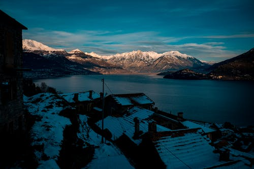 Small village near lake and snowy mountains in evening