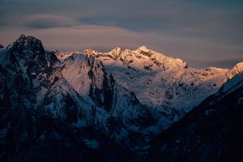 Scenic snowy highlands under cloudy sundown sky