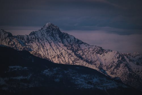 Picturesque scenery of huge rocky mountain range covered with snow under cloudy sunset sky in winter