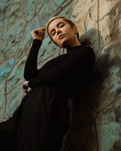 Low angle of young confident female in trendy black clothes standing in light place near shabby uneven surface while looking at camera