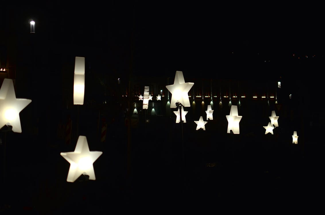 Creative star shaped garlands with glowing lamps decorating street against dark night sky