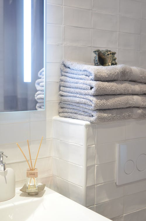Fragrance sticks and towels in contemporary bathroom