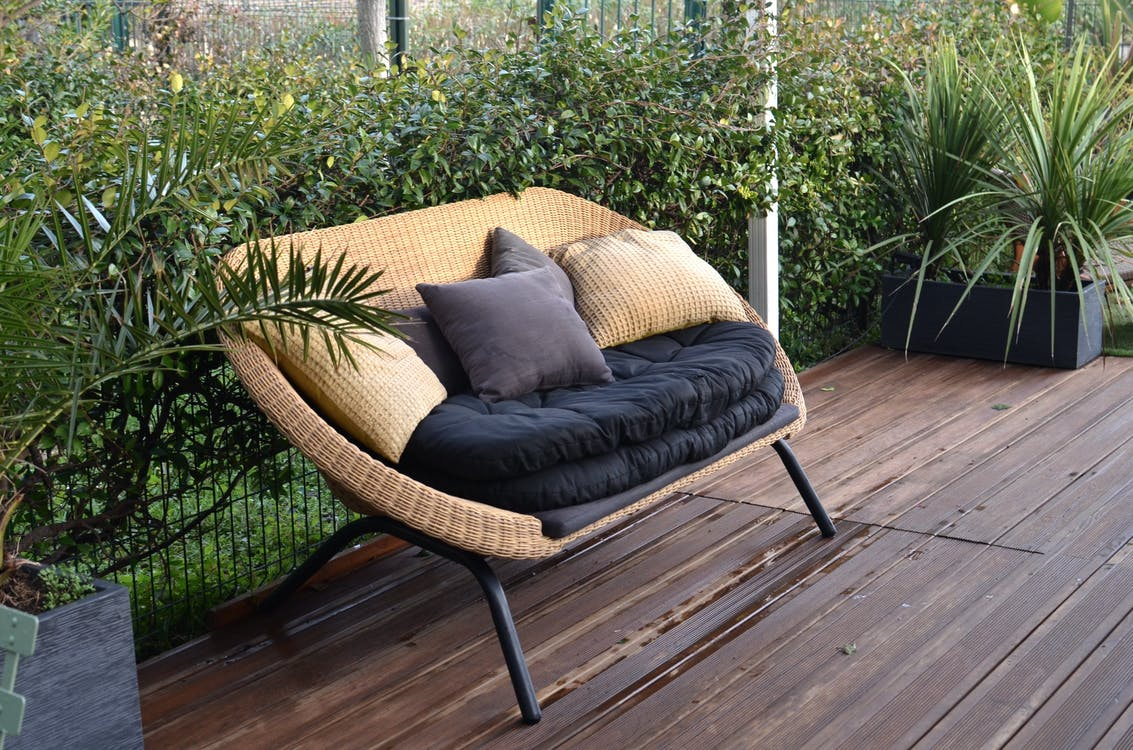 Comfortable stylish wicker sofa with soft seat and pillows placed in patio with lush green tropical vegetation in daytime