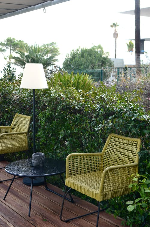 Comfortable wicker rattan armchairs with round table an lamp placed near lush green vegetation in backyard of tropical resort on rainy day