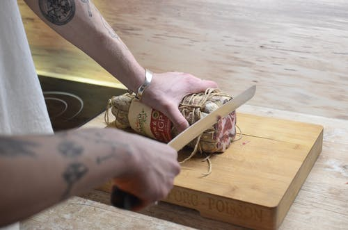 Crop man cutting meat on wooden board at home