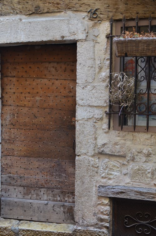 Weathered stone building with shabby doors and latticed window