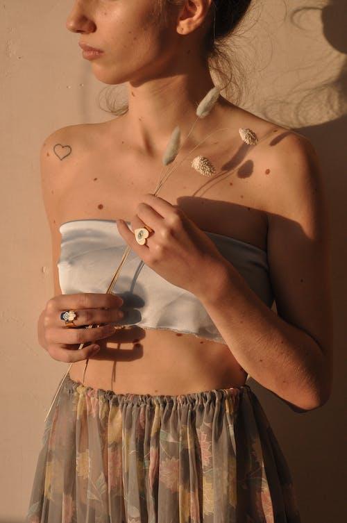 銀のネックレスを保持している黒いブラジャーの女性