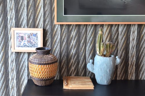 Creative wooden vase with potted cactus plant and notebook placed on table near wall decorated with framed pictures in modern apartment
