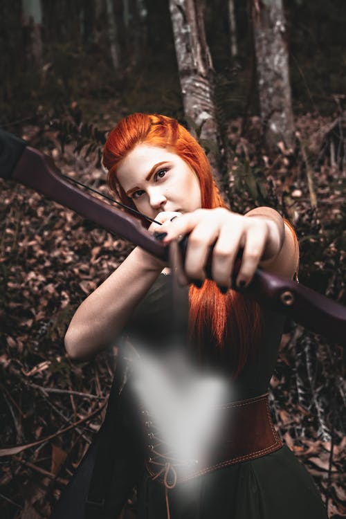 Self assured young female with long red hair in old fashioned dress shooting with bow and arrow and looking at camera in autumn forest