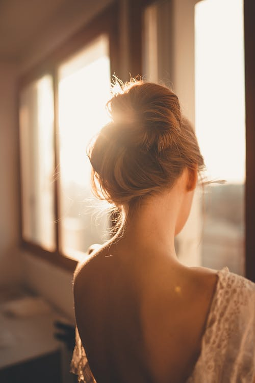 Woman in White Lace Top Looking at the Window