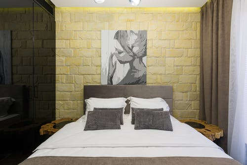 Bedroom interior with painting on brick wall in hotel