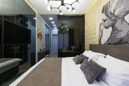 Hotel room interior with bed and painting on brick wall