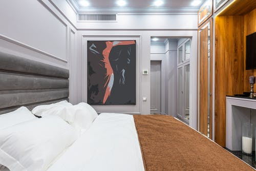 Contemporary hotel room interior with pillows and cover on bed against artwork on wall and light corridor
