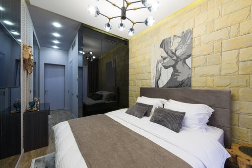Bedroom interior with bed and painting on brick wall