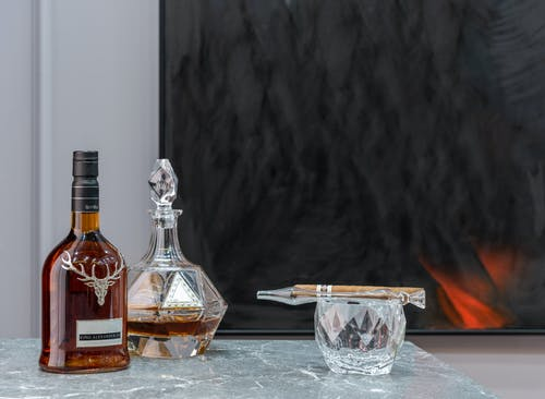 Bottle and decanter with expensive alcoholic drink near ornamental glass with cigar in house room