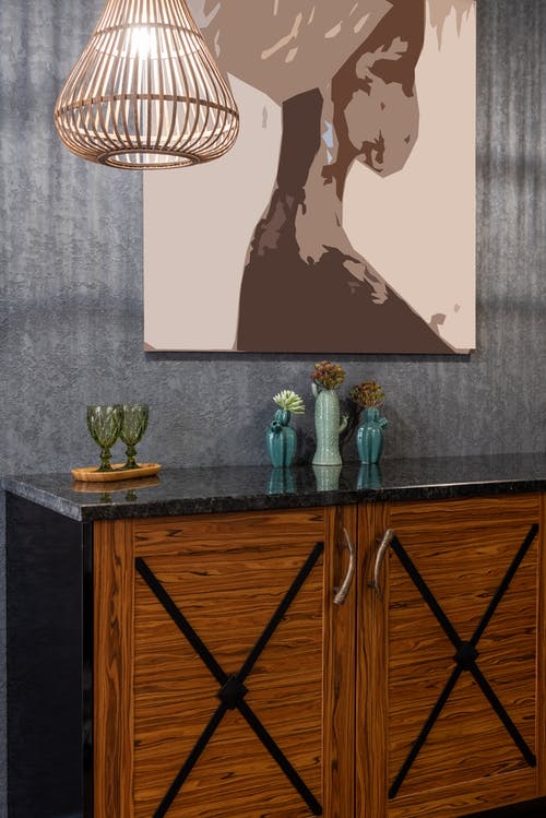 Stylish interior with painting on wall above wooden cabinet
