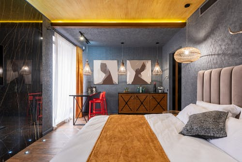 Interior of modern bedroom with comfortable bed and creative chandeliers