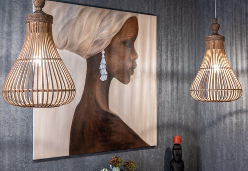 Painting of African woman on wall between shiny lamps