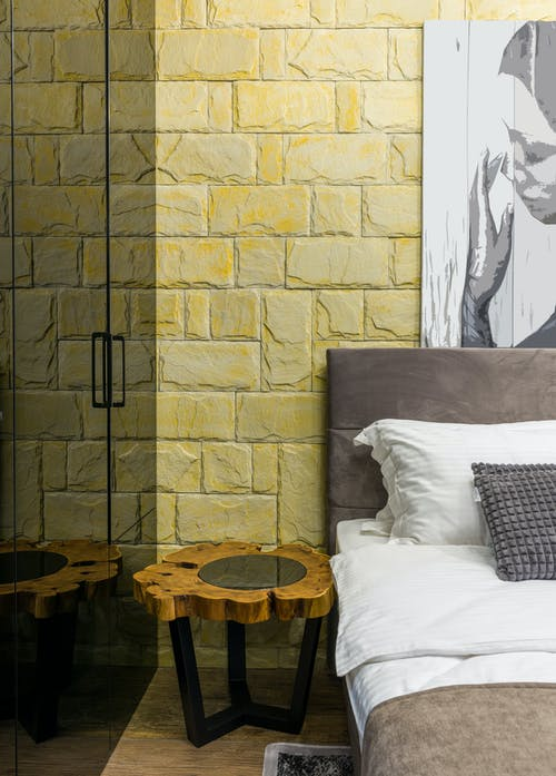 Bedroom interior with bed and artwork on brick wall