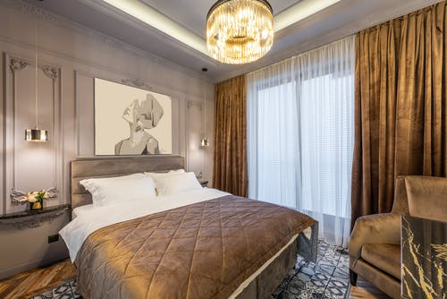 Modern bedroom interior with soft bed under shiny chandelier