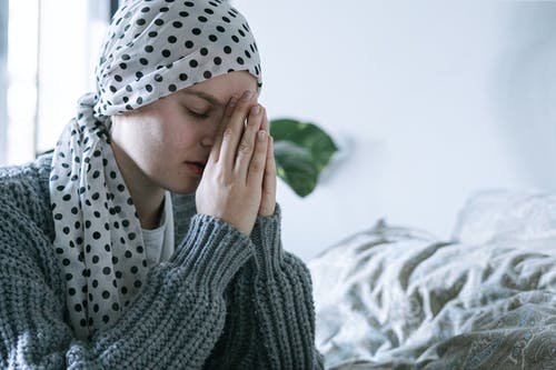 Woman in Gray Knit Sweater Covering Her Face With White and Black Polka Dot Hijab