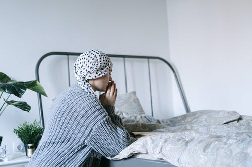 Woman in White and Black Hijab Sitting on Bed