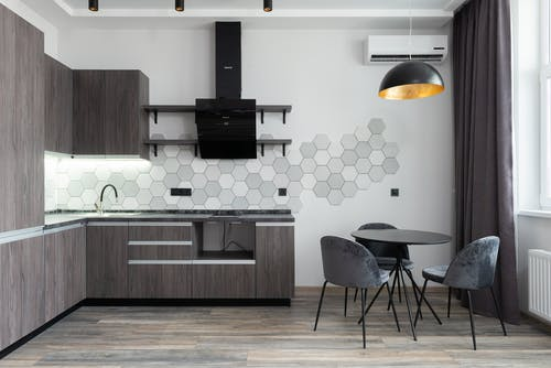 Creative design of kitchen with cupboards and cabinets under hood against table with chairs in daylight at home