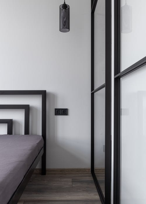 Contemporary bed with mattress and holes on parquet under lamp in house in daylight