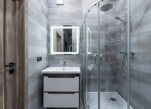 Contemporary washbasin under mirror against shower room with glass walls and tiles at home
