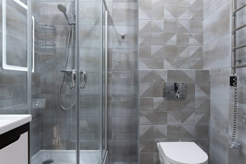 Modern shower room interior with toilet bowl at home