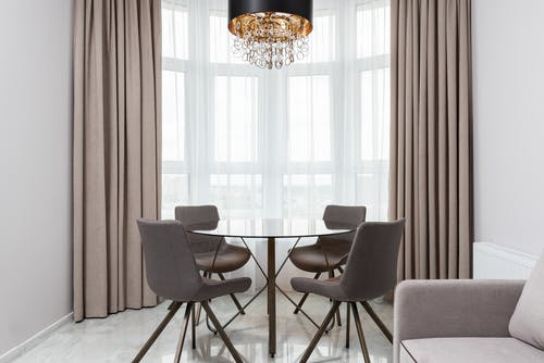 Modern living room interior with sofa against table and chairs under decorative chandelier in light house