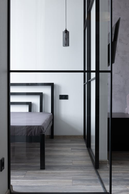 Contemporary bed with mattress and holes in house with hanging lamp and glass division in daytime