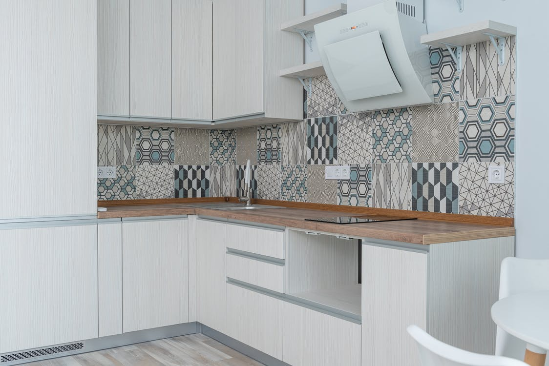 Interior of contemporary kitchen with white cabinets and wooden counter near ornamental tile on wall and modern appliances in apartment