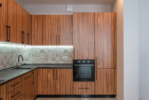 Interior of kitchen with wooden cupboards and contemporary black oven near marble counter with sink and tiled wall in light apartment