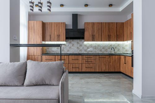 Modern kitchen with wooden cabinets and black exhaust placed near bar counter and soft sofa in light spacious room at home