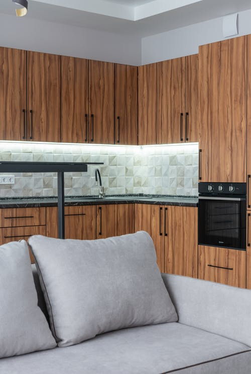 Kitchen interior with wooden cupboards and sofa