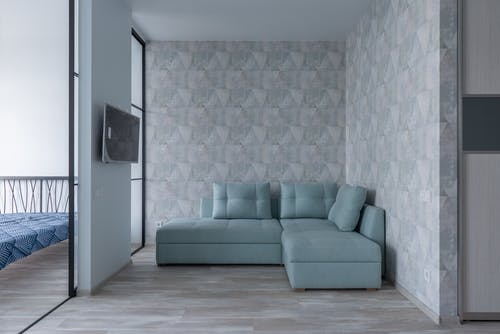 Comfortable sofa with cushions placed near wall with wallpaper and bedroom with glass wall and bed in modern flat with TV