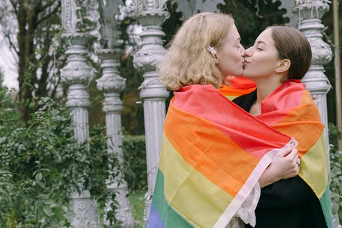 Women Wrapped with Rainbow Flag Kissing